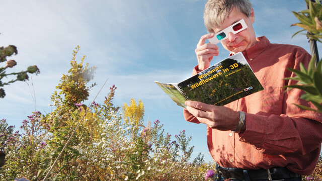 TOTALLY JUST LIKE AVATAR KIND OF! Stout professor David Tank eyes up his latest book: Wisconsin Wildflowers in 3D. It's in three dimensions, like life.