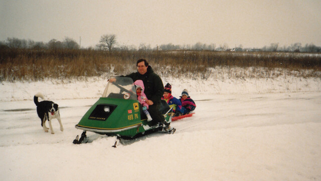 V1 Managing Editor Trevor Kupfer and his brother ride in a sled pulled by Dad's snowmobile.