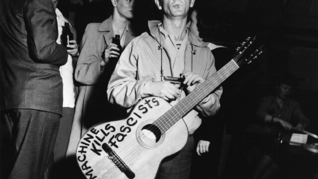 BELOW: Woody Guthrie, shown here sticking it to the man.