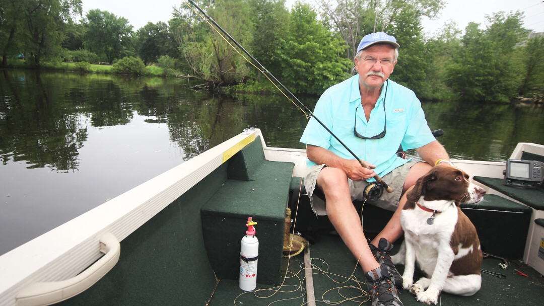 FISHFUL THINKING. Dave Carlson (shown here fly fishing at Eau Claire's Riverview Park with his dog Ellie) published his latest book, A Fish Gift, in April.