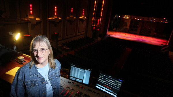 ALL THE WORLD'S A STAGE, SO LET'S KEEP IT PROPERLY LIT. Local light designer Paula Dinkel stands before The State Theatre's light board.