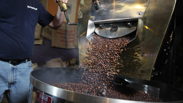 A roaster at Coffee Grounds prepares beans from the Farmer to Farmer program for brewing and drinking.