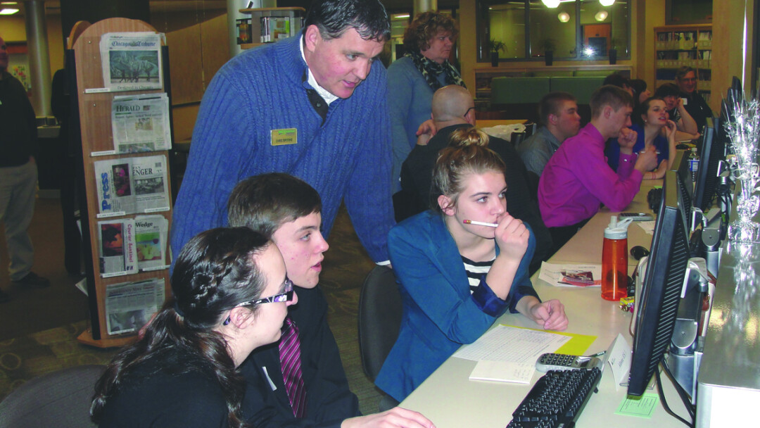 TEENS WITH SCREENS. Volunteer Chris Brooke of WESTconsin Credit Union works with local students during a Junior Achievement event at the Chippewa Valley Technical College Learning Center.