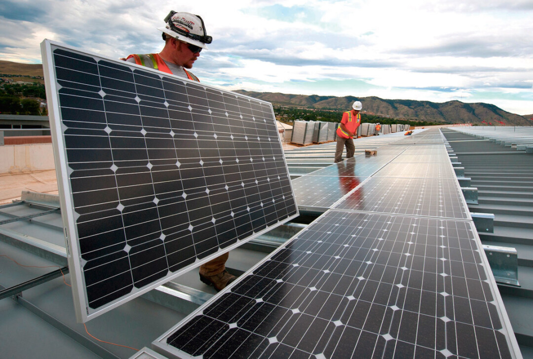 Workers install  solar  panels as part of a U.S. Department of Energy/Xcel project  in Colorado