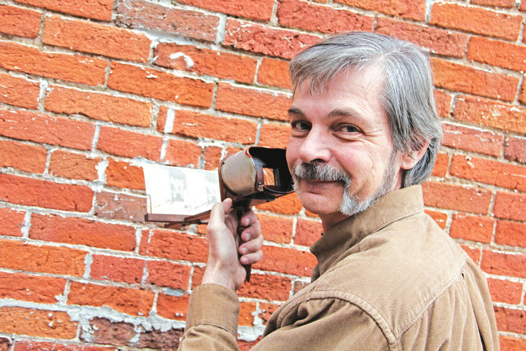 VICTORIAN ERA VIRTUAL REALITY GOGGLES. Author David Tank shows off a vintage stereoscope containing one of the 19th century Christmas images that inspired his new book for young readers, Secret Santa.