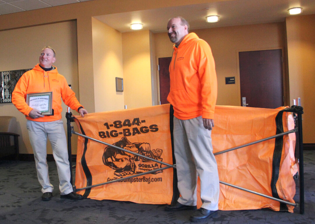 IN THE BAG. Steve Faacks and Chris Hansen show off an example of their Gorilla Dumpster Bag after being announced as winners of the 2015 Idea Challenge Dec. 3 at UW-Eau Claire.