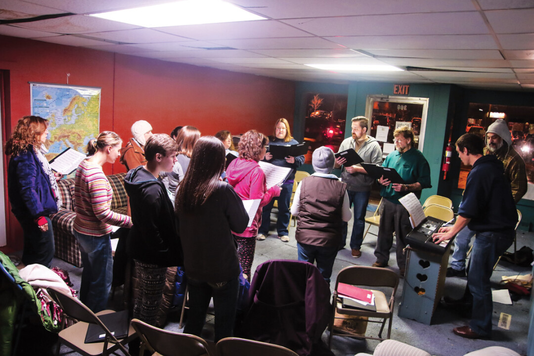 SINGIN' TOGETHER. Michael Rambo leads a crew of community singers as the CollECtive Choir rehearses together for an upcoming show at The Plus on Dec. 13.