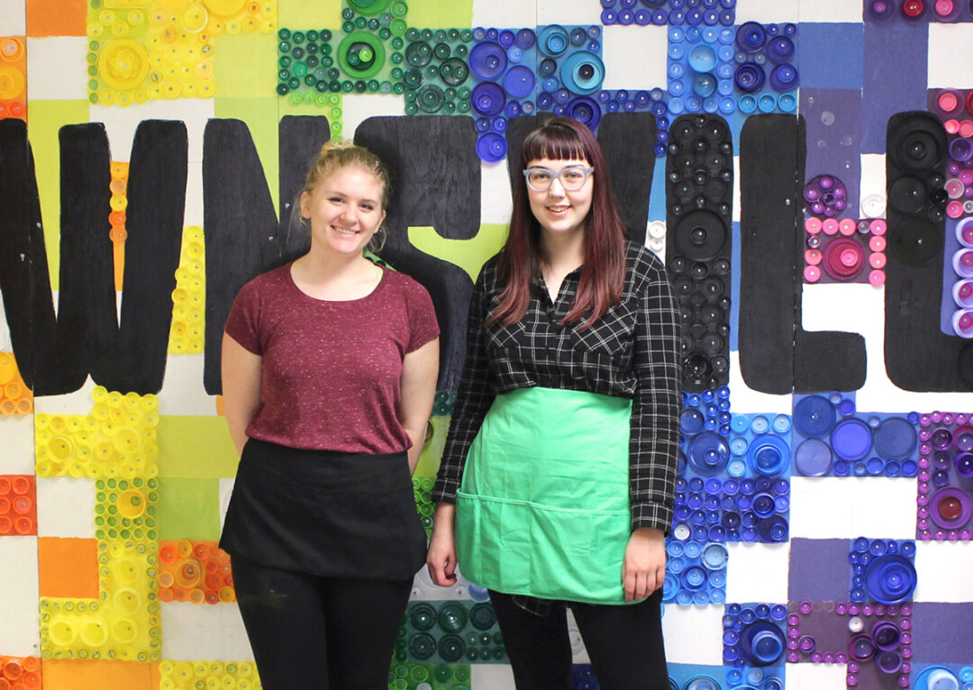 PUT A LID ON IT. Two UW-Stout art majors, Abby Henderson, left, and Grace Rogers, right, created a mural at Downsville Elementary School with the help of Downsville students and approximately 7,000 bottle caps.