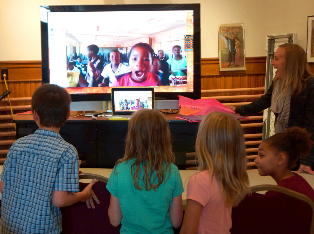LONG-DISTANCE CONNECTION. Menomonie children connect with children in Botswana via Skype during a PAINT International art session at the Mabel Tainter Center for the Arts. At right is Megan Steinkraus, PAINT coordinator, Menomonie elementary art teacher and UW-Stout alumna.