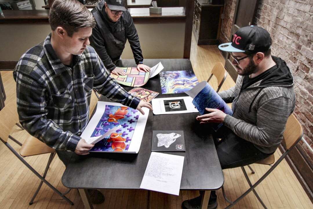 513FREE staff members (left to right) Michael Sandvig, Jesse Hamble, and Jonny Stoll look over works of art submitted by inmates for The Pen Project magazine.
