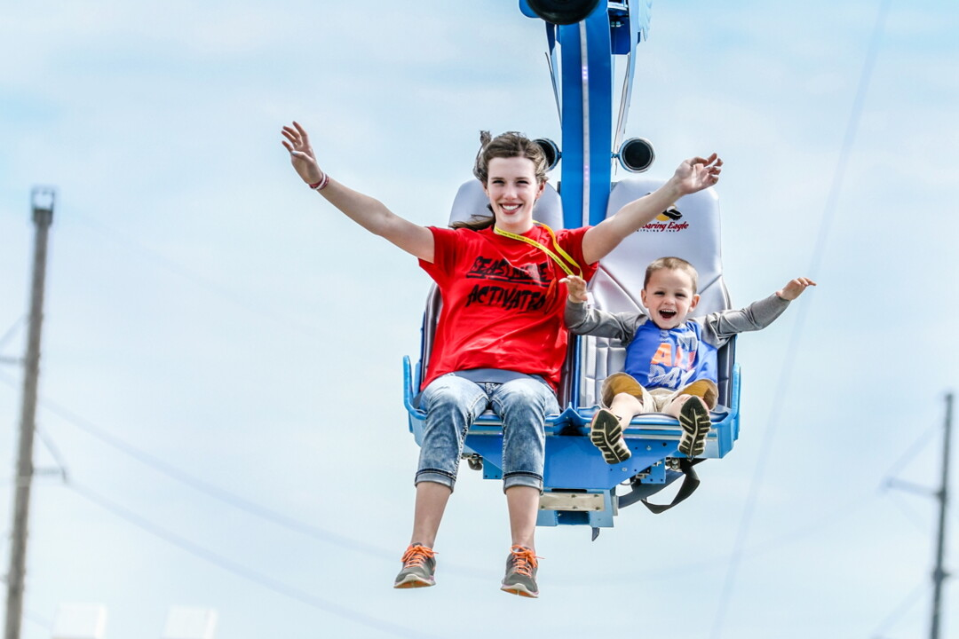 IT'S HIP TO ZIP. A pair of happy zip-liners try out the new motorized zip-line at Action City in Eau Claire. Open as of Saturday, May 6, the ride is 130 feet high and 700 feet long. The amusement center also opened up a new outdoor go-kart track on the same day.