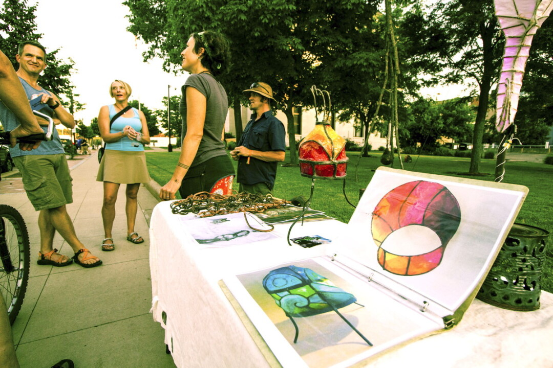 STREET ART. Brianna Capra and Brent Gonyea, center, were among the artists who displayed works in downtown Eau Claire during the Prex Claire festivities.