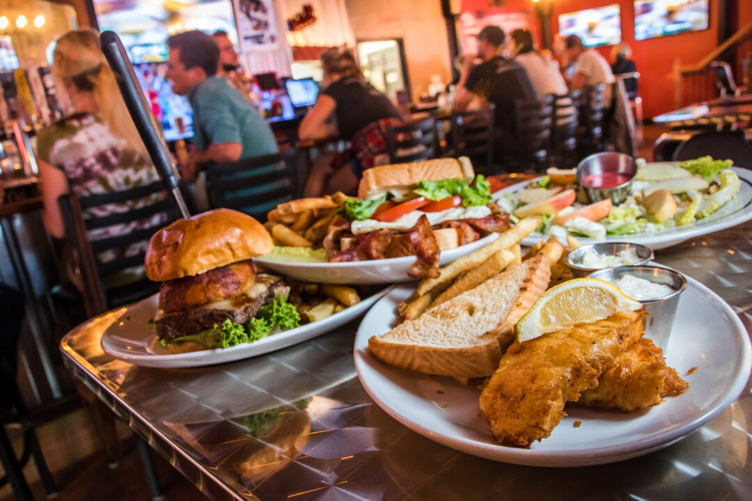 ZONED FOR FLAVOR. The District (newly opened at 101 Graham Ave. in Eau Claire) offers up an array of robust burgers and sandwiches (such as the Farmhouse BLT, far right), many of them paired with a beer suggestion.