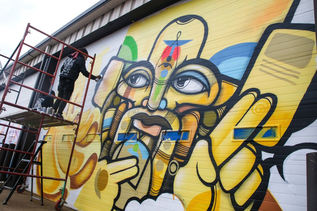 A muralist creates a new work of art during the Uptown Art Jam on Oct. 21 at Artisan Forge Studios in Eau Claire.
