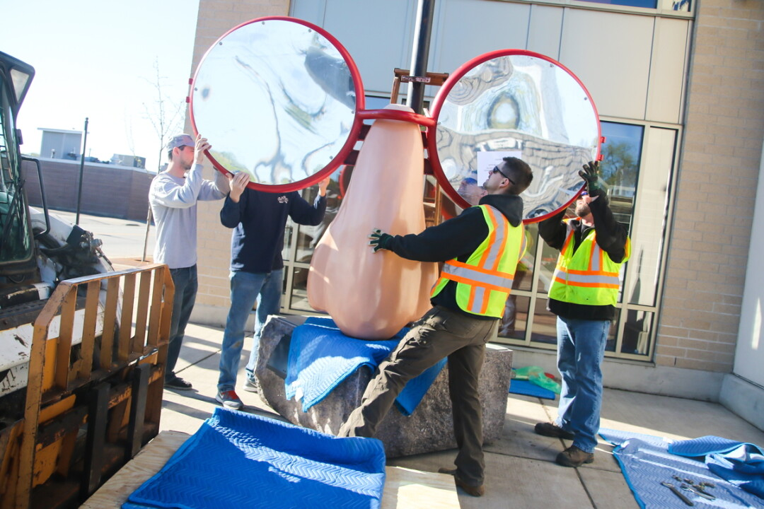 NOSE TO THE GRINDSTONE. Workers install a piece of artwork for the 2016 Sculpture Tour Eau Claire.