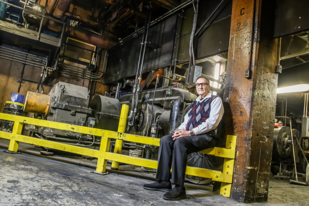 EXPLORING THE FACTORY.Jack Zais, who worked in maintenance at the tire plant for 25 years, sits before a Banbury mixer, for which the building was named.