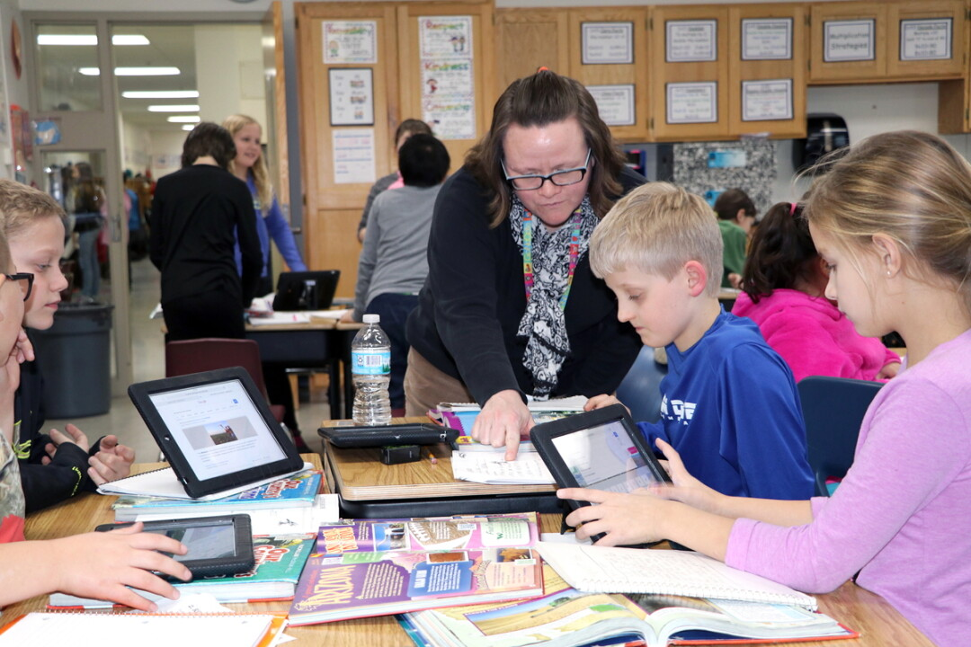 LET'S DO THIS. Beth Duellman (above left) works with fourth-grade students in a project-based learning environment at Sam Davey School. A group of Eau Claire parents wants to transform the former Little Red School (above right) into public charter school that would provide a similar environment for middle school students.