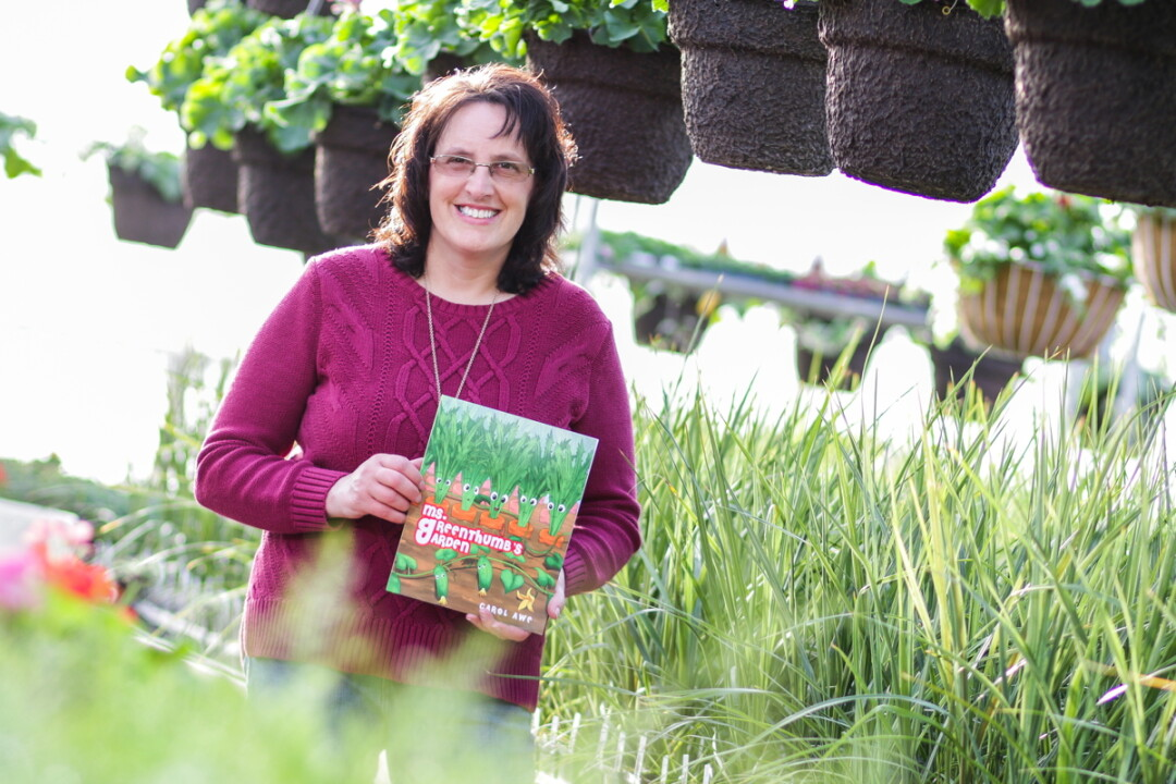 IN THE GARDEN. Carol Awe, author of Ms. Greenthumb's Garden, shows off her debut story among greenery.