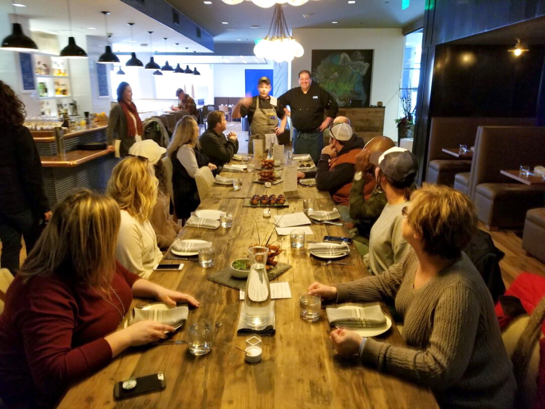 EATING UP HIS WORDS. Participants on a recent Downtown Eau Claire Food and History Tour listened before sampling at The Informalist, 205 S. Barstow St.