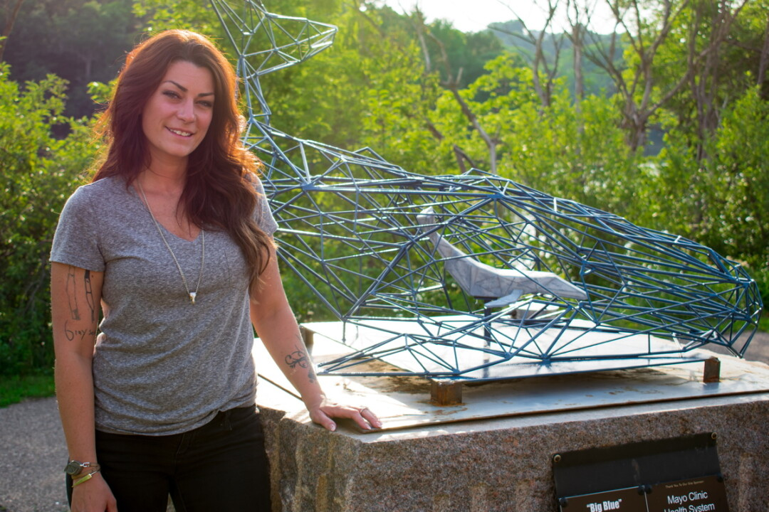 "ALL'S WELL THAT WELDS WELL. Local artist Kate McLean stands by a piece she made for the 2018 Eau Claire Sculpture Tour, installed near Mayo Clinic Health Systems across from Half Moon Lake. The sculpture, a welded creation entitled ""Big Blue,"" is an example of the environmental advocacy that inspires much of her work. The whale is several feet across, assembled from many triangles and trapezoids."