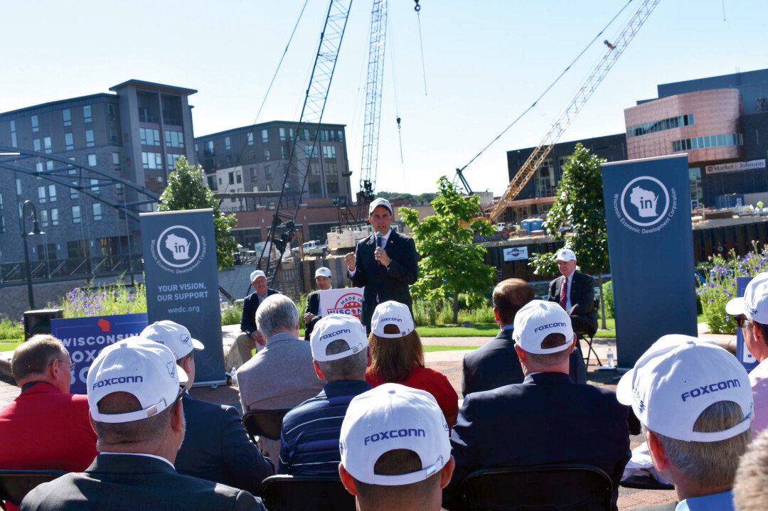 "HUB HUBBUB. Gov. Scott Walker, center, speaks at Phoenix Park July 16 at an event annoucing Foxconn Technology Group's plans to create a ""technology hub"" in Eau Claire, part of which will be inside the Haymarket Landing building, which is at the left side of the photo behind Walker."