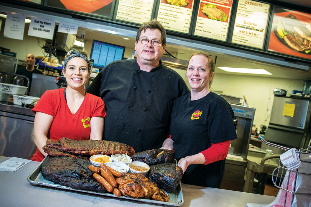 LOW AND SLOW UNTIL IT'S GOOD AND READY. Karl Hartkemeyer (center), owns Karl's Bar-B-Q Express in Chippewa Falls. The menu features brisket, ribs, and turkey – and chicken's on the way.