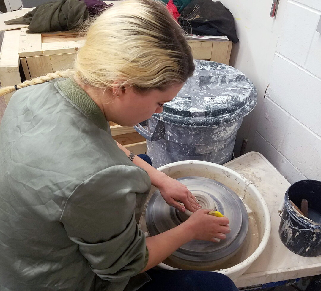 "KEEP ON BOWLIN'. Sarah Bennett fashions a bowl at the potter's wheel in her UW-Stout studio. Despite her apparent ease and grace, she points out, ""It took me years and years of practice to get to this point!"""