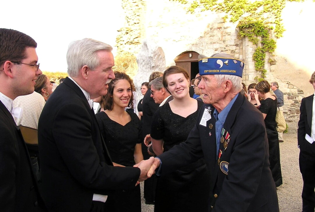 Dr. Gary Schwartzhoff, second from left, meets a veteran on the 60th anniversary of D-Day in France. He will lead the UW-Eau Claire Alumni Choir when it performs this summer at the 75th anniversary of D-Day.