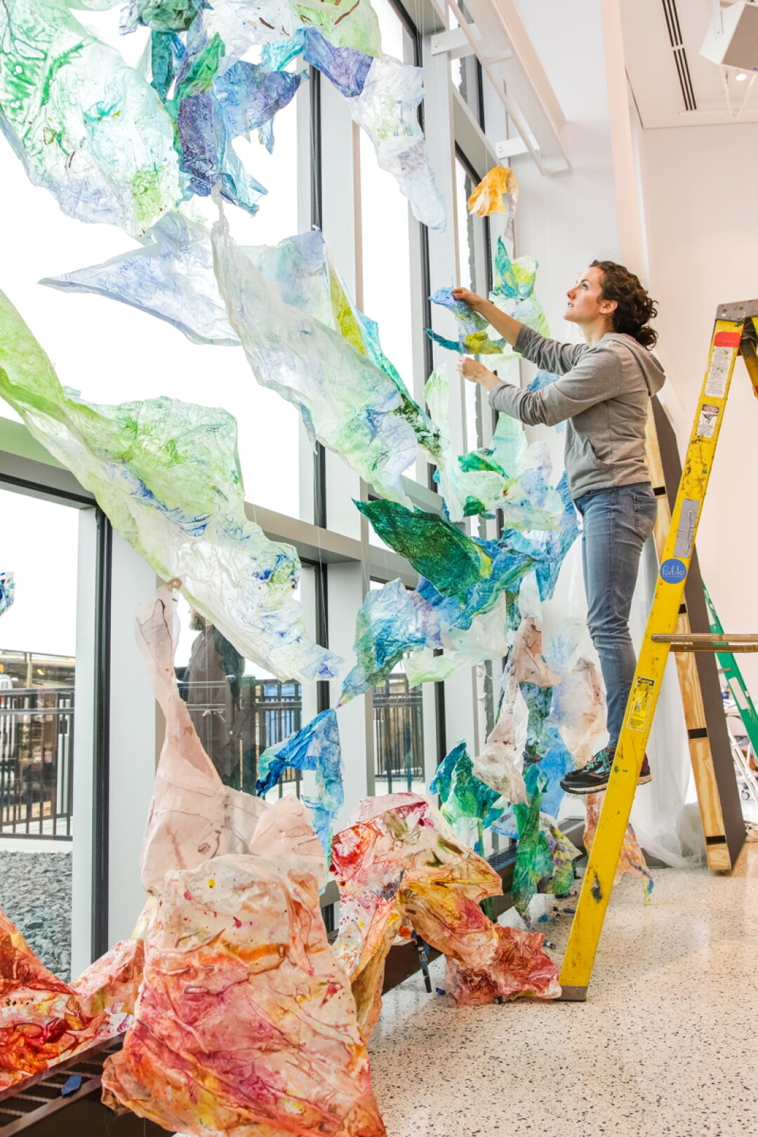 "JUST HANGIN' AT THE PABLO. Artist Holli Jacobson installs part of ""NOW: Emerging Artists of the Chippewa Valley,"" a new exhibit that runs through July 12 at the Pablo Center at the Confluence."