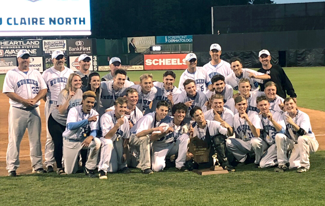 The Huskies pose with their championship trophy on June 13