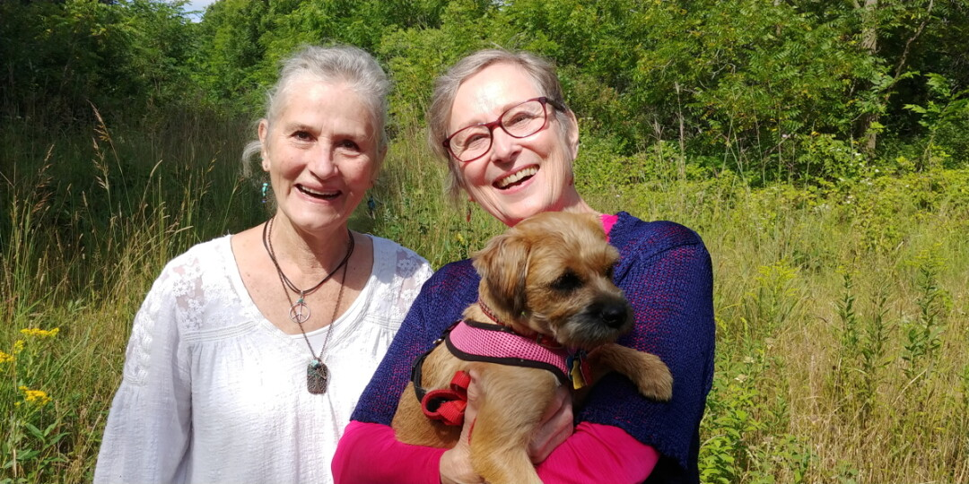 HOW THE WEST WAS FUN. Cheryl Leonard (left) and Diane Omtvedt (right), of Eau Claire's Upper Westside neighborhood, often take their pooches for easy strolls through the forested parcel between 11th Street, the High Bridge Trail, and Bolles Street. Also pictured is By Golly Miss Molly, Diane's furry companion.