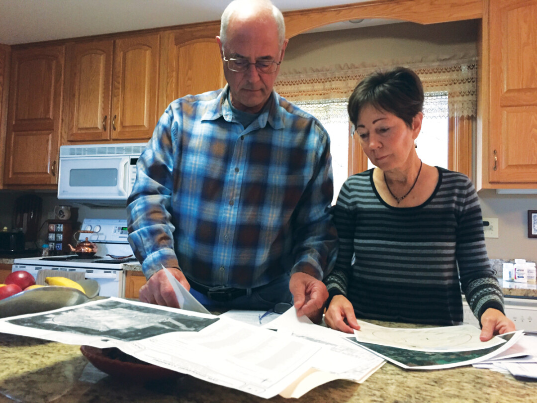 Dennis and Kathy Campbell look at paperwork related to the proposed expansion of the landfill, which is about half a mile from their house.