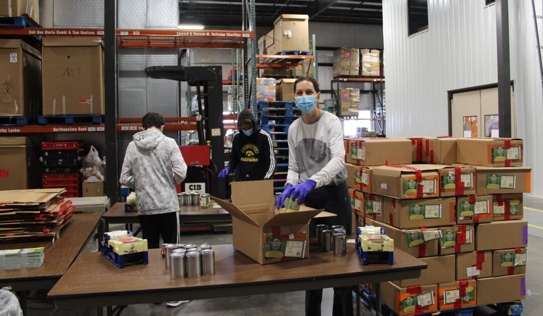 Volunteers pack emergency food distribution boxes at Feed My People Food Bank in Eau Claire. (Source: Facebook)