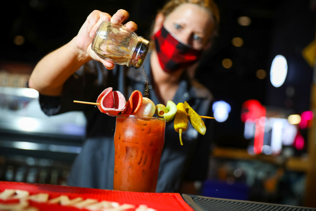 A bartender prepared a drink while wearing a face mask at Stout Craft Co. in Menomonie.