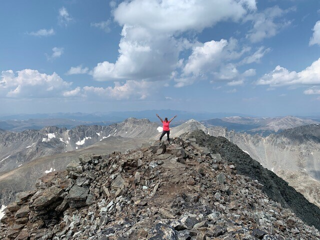 WOMEN CAN DO ANYTHING. And for Kathy Wright, the general manager of Country Jam, that includes climbing to the summit of a 14-er. Don't look down, Kathy!
