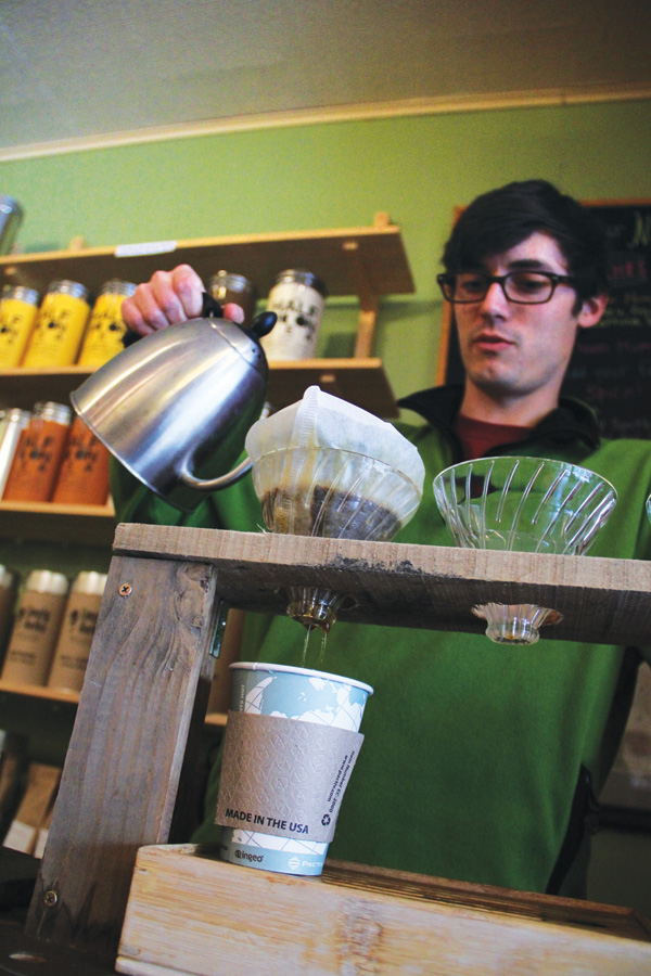 Half Moon Tea & Spice manager Colin Carey pours a cup of Kickapoo coffee, measured precisely for optimum taste.