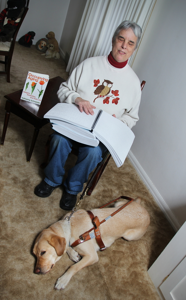 Author Katherine Schneider displays the Braille edition of her new book, Occupying Aging.