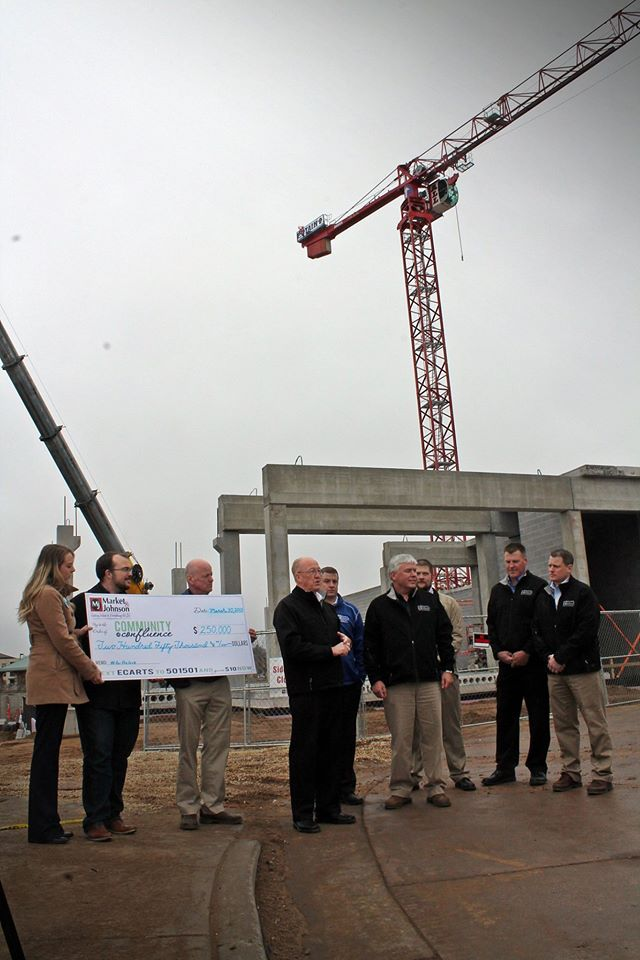 A big check from Market & Johnson –  at the Haymarket Landing sit on March 30. Image: Community for the Confluence