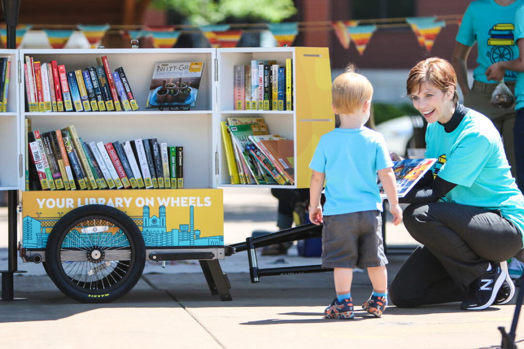 PAGING YOUNG READERS. L.E. Phillips Memorial Public Library Director Pamela Westby shows off the contents of the library's new BookBike during a jaunt to Phoenix Park on a recent summer morning. The custom-made bike trailer, which can hold about 100 books, will be pedaled to events by librarians.