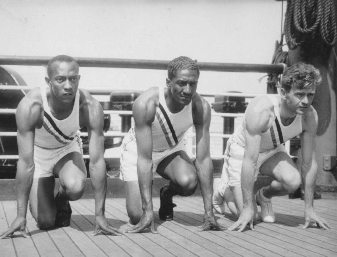 Metcalfe (center) with Jesse Owens and Frank Wykoff on the deck of the S. S. Manhattan as the team sailed for Germany in 1936. Image: Wikimedia Commons