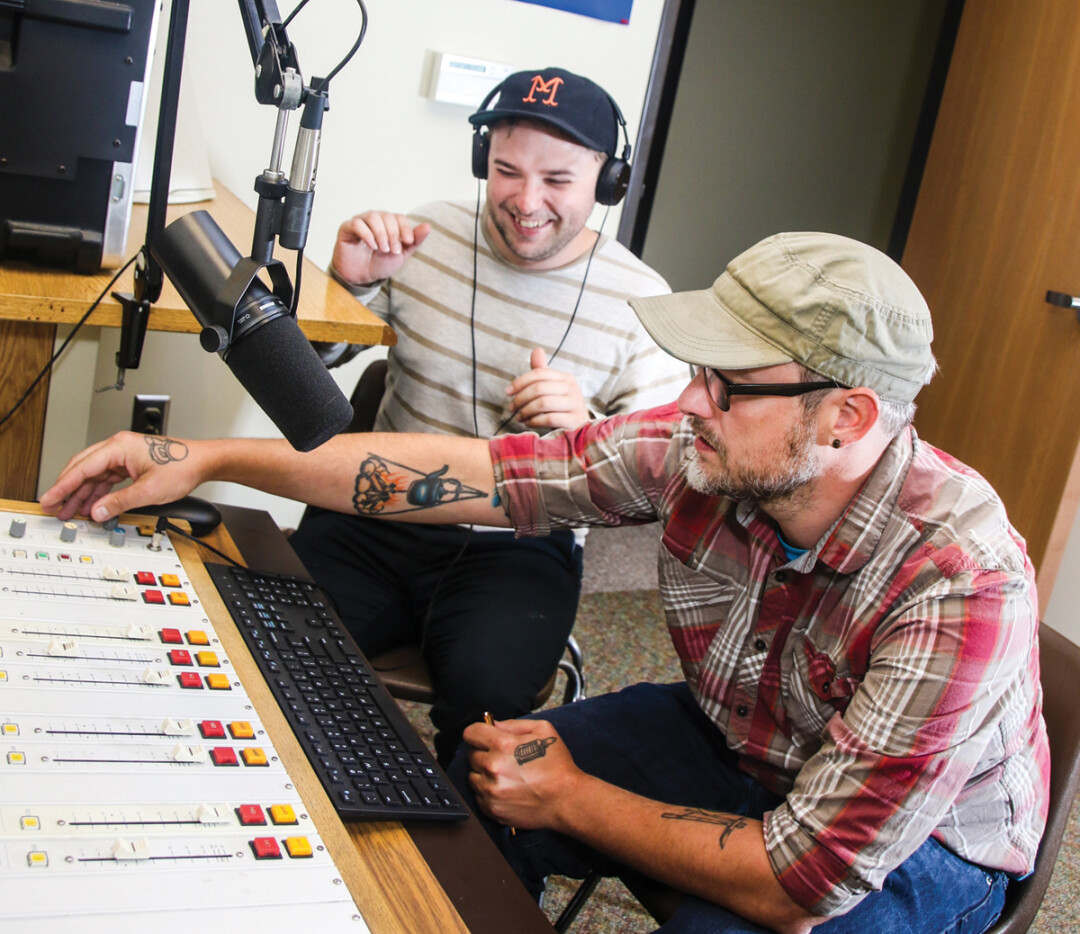 In thier cramped studio space, Blugold Radio station manager Scott Morfitt (right) works the dials while social media manager Jordan Duroe thoroughly enjoys himself.