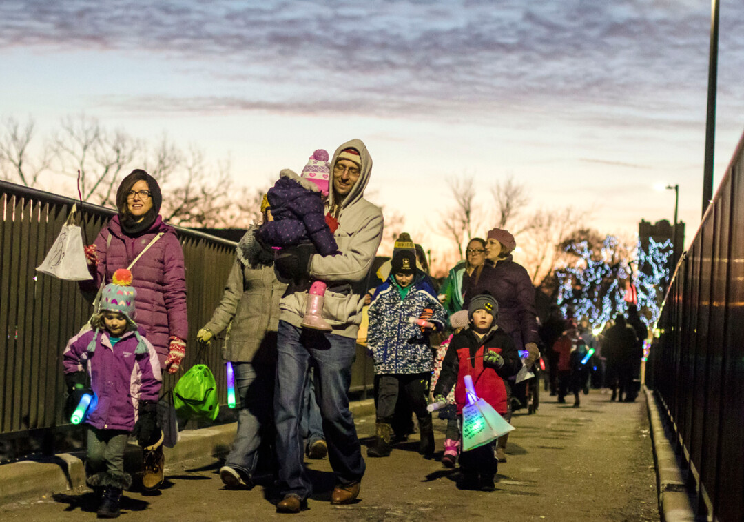 On New Year's Eve, families take to the Grand Ave. walking bridge in downtown Eau Claire carrying homemade paper lanterns.