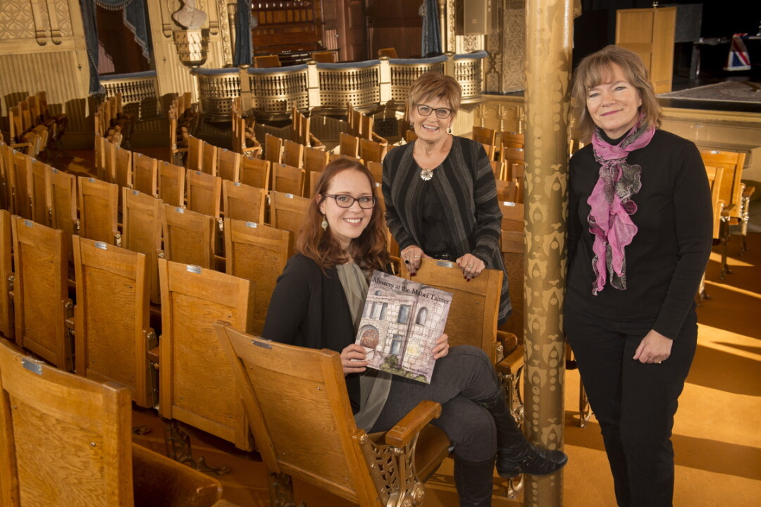 illustrator Taylor Kysely, board member Judy Foust, and author Mary Heimstead created a book set at the Mabel Tainter Theater.